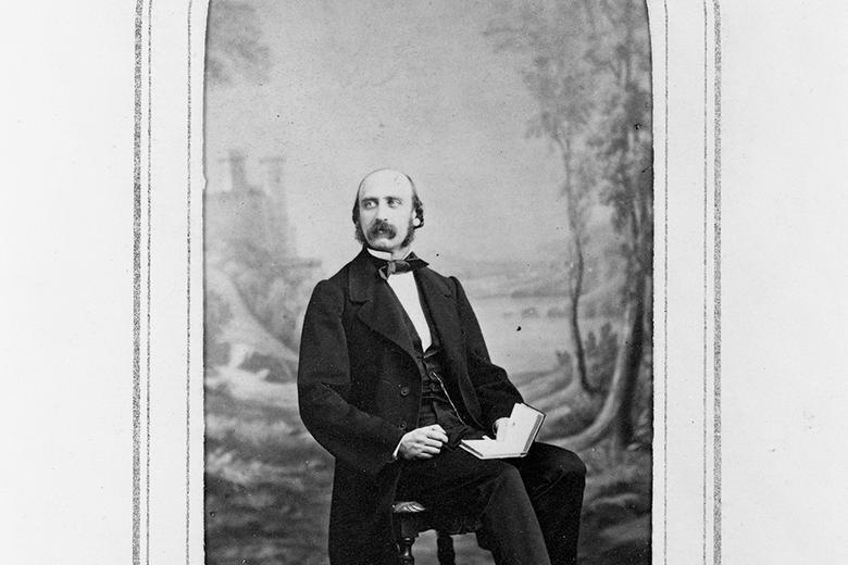 Black and white portrait photograph of a man with a moustache