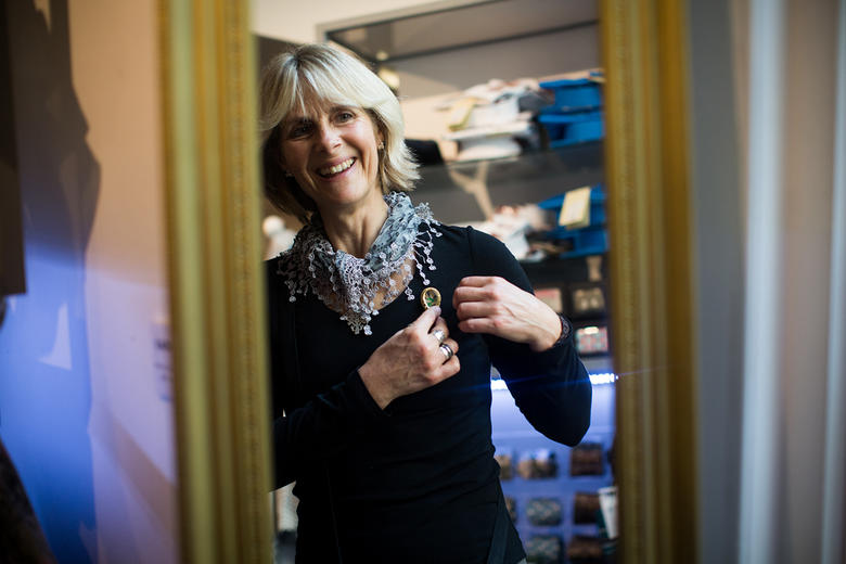 A woman looks in the mirror to try on a brooch in the Ashmolean Shop