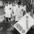 A photograph of five men in white coats wearing masks, holding cleaning supplies on a pavement next to a sign that says 'BE CLEAN'