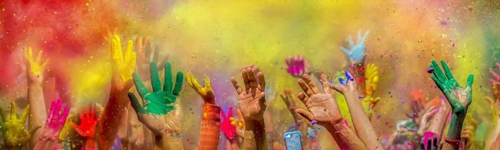 Colourful powders fill the air, and hands covered in powder and paint reach upwards, as part of Holi celebrations