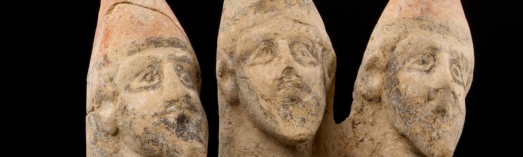 A stone sculpture of three male heads