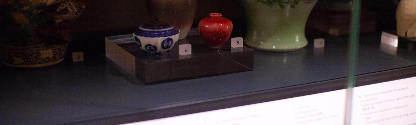 A small red Japanese Vase by Miyagawa Kozan 1890 in dimly lit Gallery Case