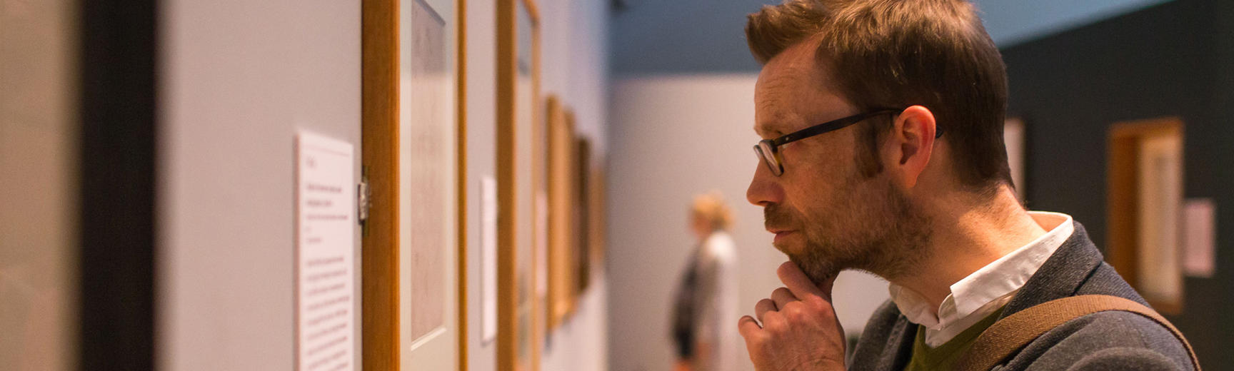 A man takes a closer look at an artwork on display on a gallery wall
