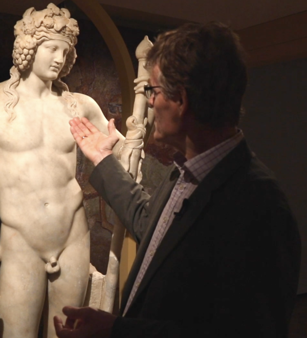 Dr Paul Roberts gestures to a Statue of Bacchus