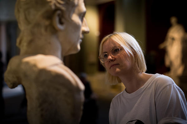 A woman looks closely at a bust in the sculpture gallery