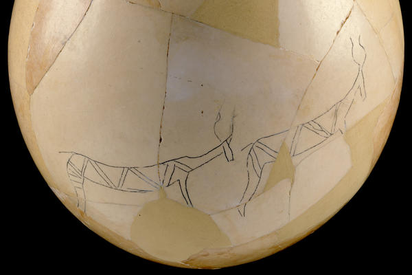 A reconstructed ostrich egg decorated with line drawings of animals