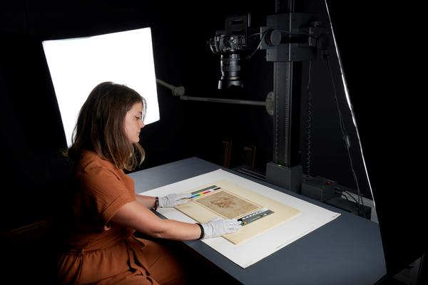 Staff member in the process of photographing a work on paper