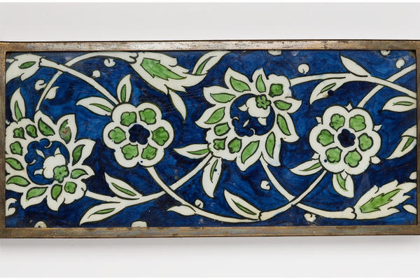 A blue tile patterned with a green flowers.