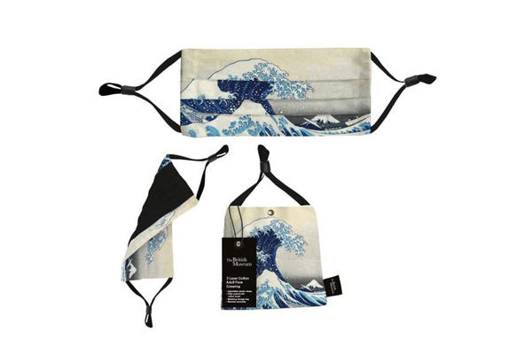 A face mask with a design depicting a large blue and white wave towering high above the view of Mount Fuji in the distance