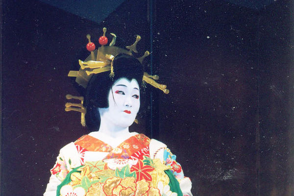 A standing figure in traditional Japanese dress of green, gold and red