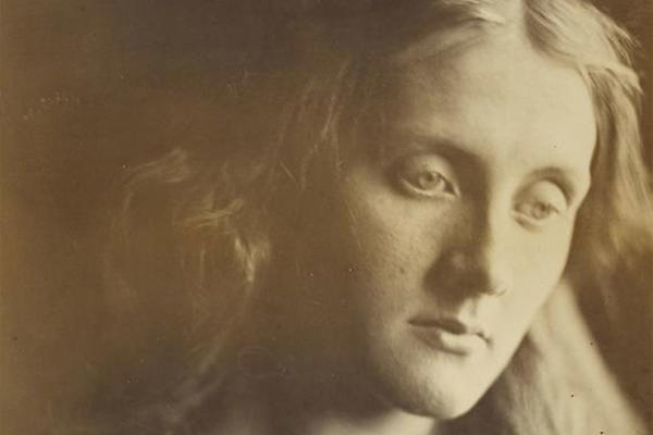 A sepia photograph of a woman gazing, looking lost in thought