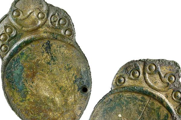 Flat bronze discs with short decorated handles