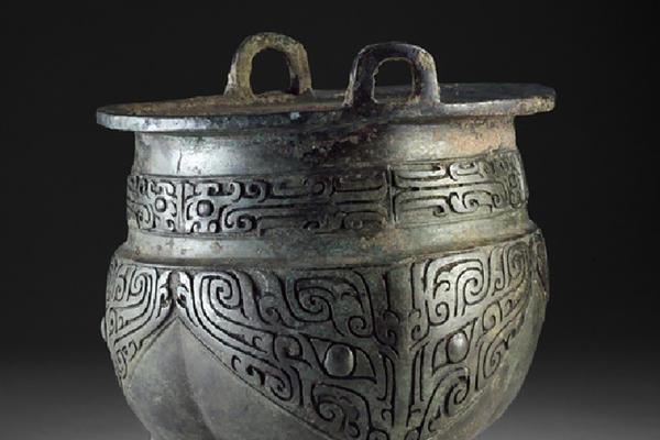 A pot like vessel decorated in taotie masks