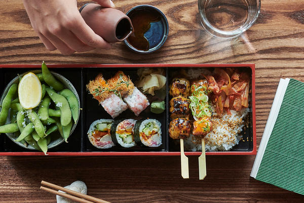 View from above of a selection of sushi on a wooden table, chopsticks, with a hand pouring out a drink