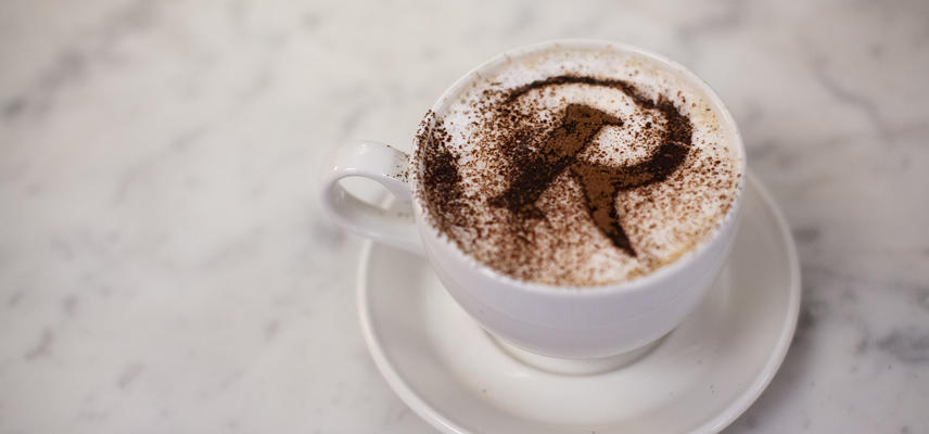 A coffee with a chocolate dusted R