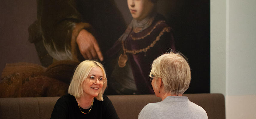 Two women have a coffee in the cafe with a Rembrandt painting behind them