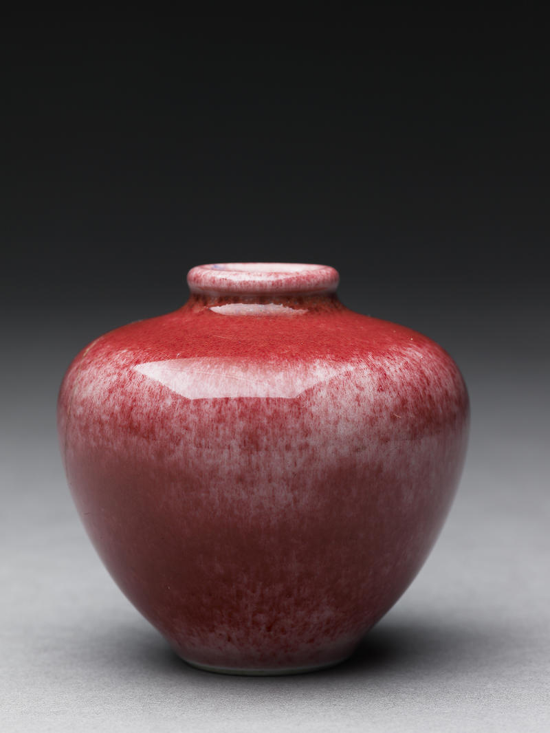 A small round Japanese vase with red glaze and a narrow spout