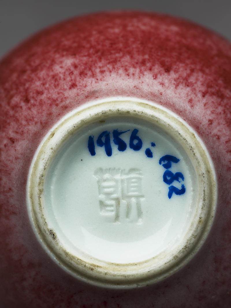 A close up image of the bottom of a red vase with a stamp from Kozan's workshop and an accession number in blue ink