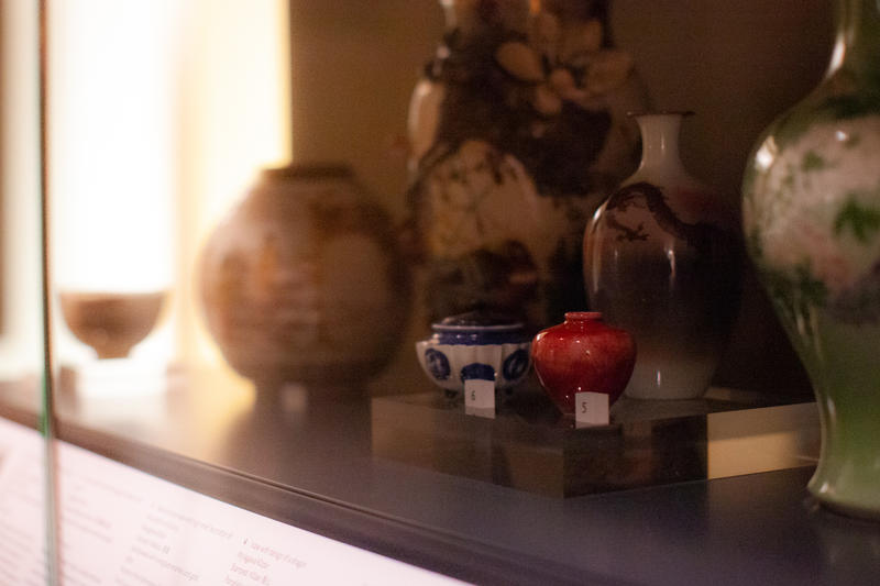 A dimly lit photo of Japanese vases in a case, with small red vase in central focus