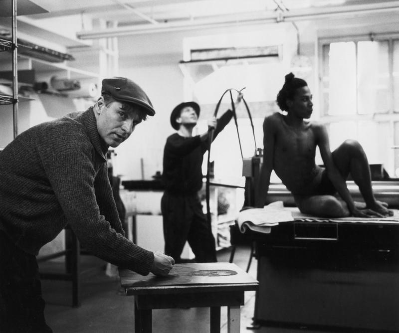 Black and white photograph of the artist Rainer Fetting, and two others, in a studio in 1989