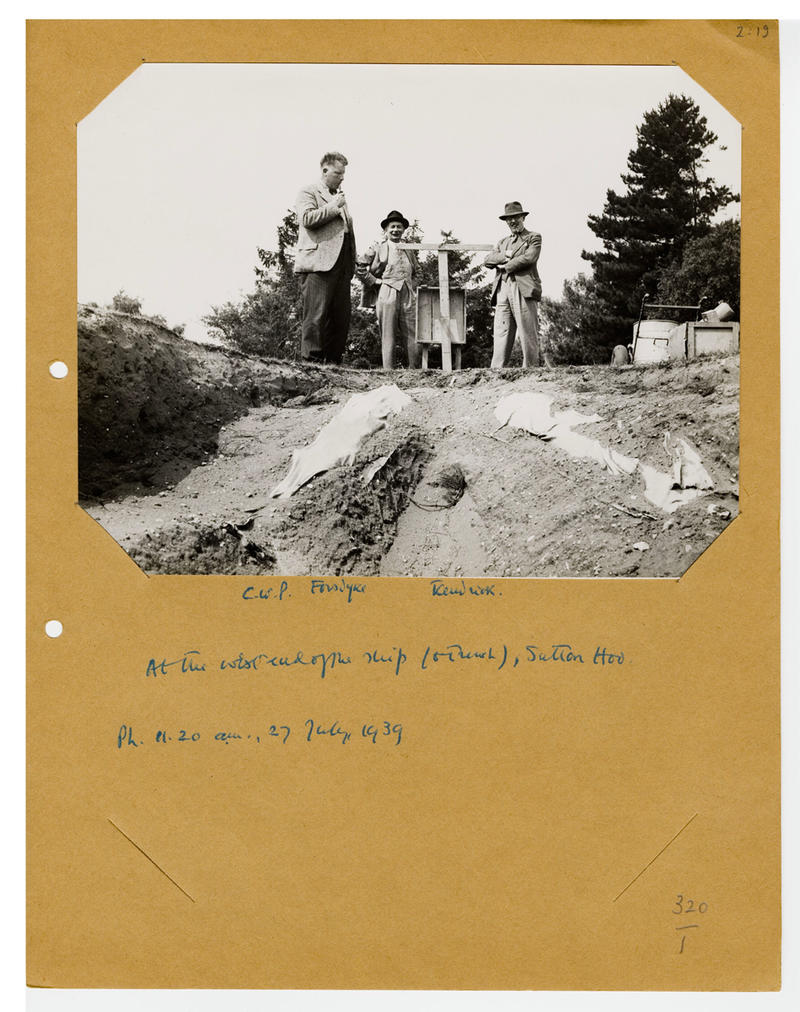 A black and white photograph of figures next to an archaeological dig, with handwritten notes underneath