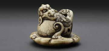 Netsuke in the form of a rain dragon coiled around a mokugyō, a Buddhist percussion instrument from the Ashmolean collections
