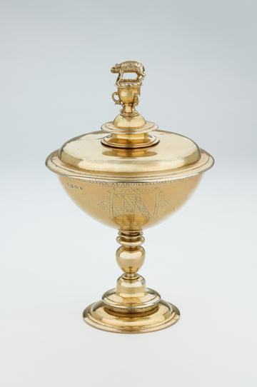 A gold-coloured cup and lid, with a small pig figure perched on the very top