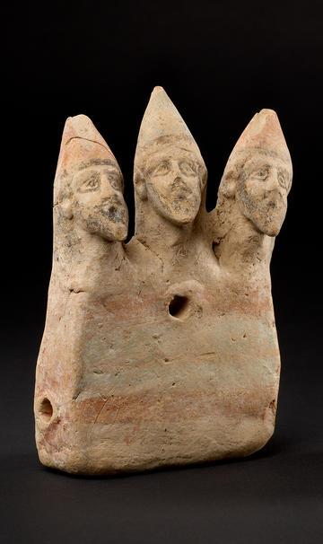 A ceramic sculpture of three male heads
