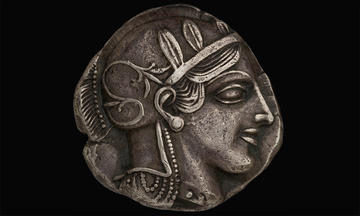 Silver coin decorated with profile of Greek warrior