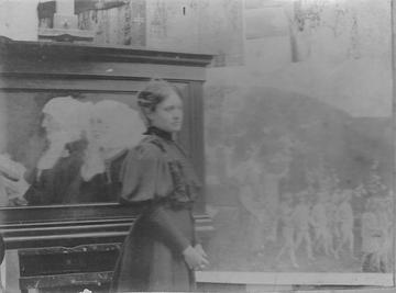 Blacka and white photograph of Elizabeth Sonrel standing by her painting
